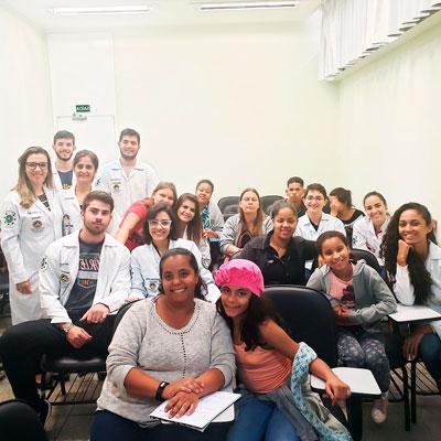 Foto em uma sala com alunos e pacientes da turma da Christine